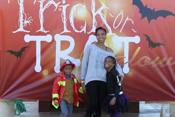 Family standing in front of the Trick-or-Trot sign.