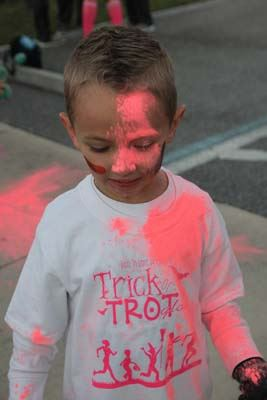 A little boy with pink powder from color run.